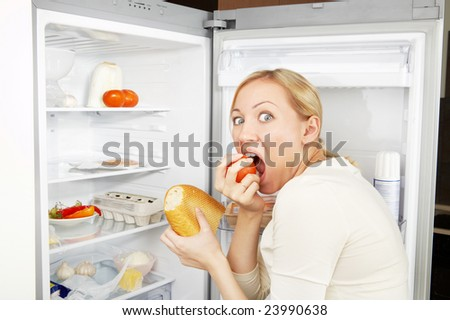 The woman greedy eats meal against an open refrigerator - stock photo