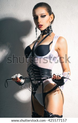 The woman in a beautiful ladies' fetish lingerie stands with a whip and looking at us - stock photo