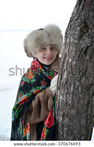 The woman in a pavlovo-posadsky scarf and a fur cap hides behind a tree - stock photo
