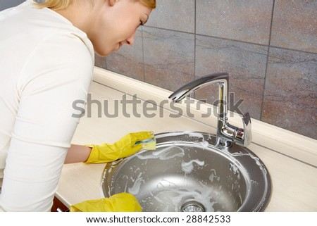 The woman in gloves cleans a bowl on kitchen - stock photo