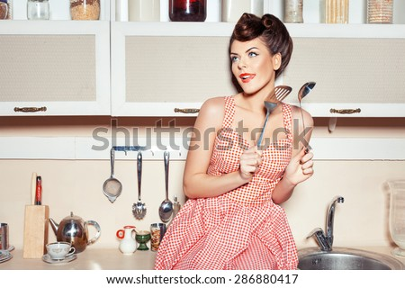 The woman in the kitchen. In the hands holding tools for cooking food. She flirts. - stock photo