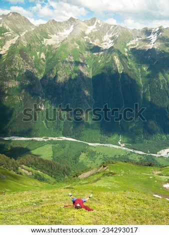 The woman lies on a flowering field hands outstretched against the backdrop of the majestic mountains of the North Caucasus - stock photo