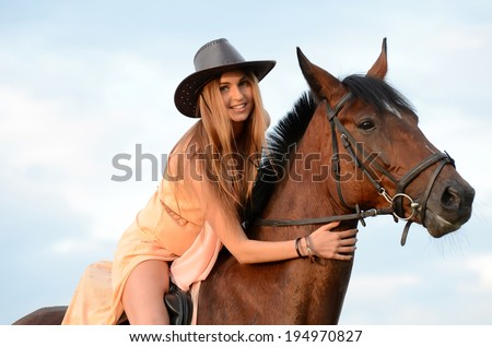 The woman on horse against the sky - stock photo