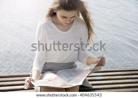 The woman reading newspaper by the lake - stock photo