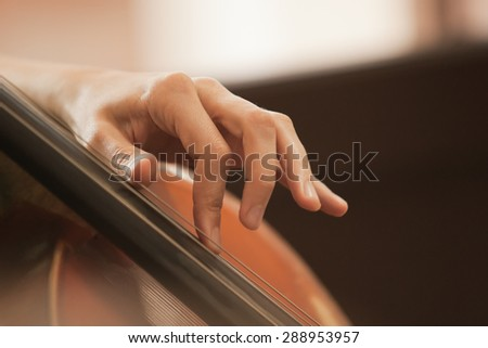 The woman's fingers on the strings of a cello - stock photo