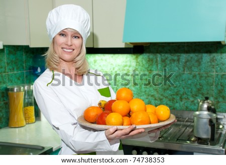 The woman the cook with a tray of fruit on kitchen - stock photo