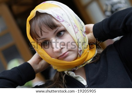 The woman ties a kerchief round one's head - stock photo