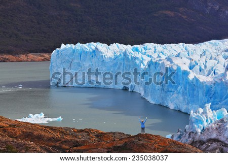 The woman - tourist admire the white-blue icy splendor. Giant lake Perito Moreno glacier - stock photo