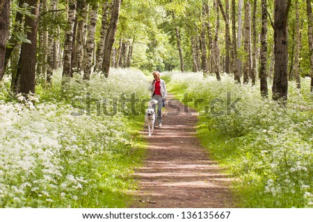 The woman walks with a dog in park - stock photo