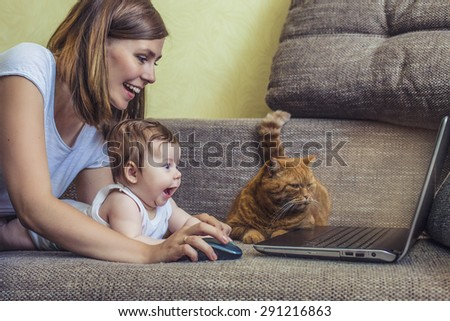 The woman with a baby and a cat at the laptop lying on the couch - stock photo