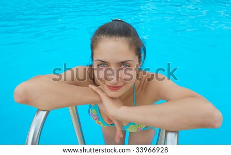 The woman young and beautiful enjoys rest in pool - stock photo