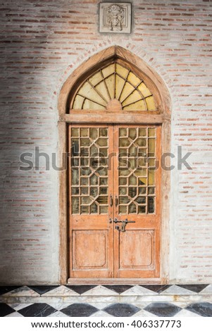 The wooden front door of a home with glass panels to each side and a brick porch. The glass is reflecting the homes opposite the door. Vertical shot. - stock photo