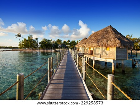 The wooden road over the sea to the tropical island.  - stock photo