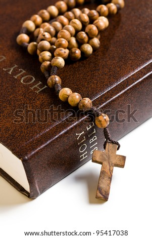 the wooden rosary on the Bible - stock photo
