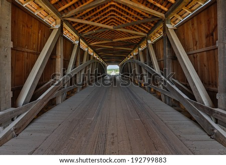 The wooden supporting architecture of covered bridge is viewed from the inside. This is Parke County, Indiana's Sanatorium Covered Bridge. - stock photo