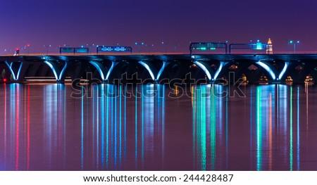 The Woodrow Wilson Bridge at night, seen from National Harbor, Maryland. - stock photo