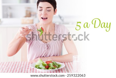 The word 5 a day against smiling brunette woman eating salad - stock photo