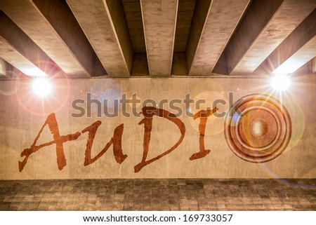 The word audio with bass speaker as graffiti on the support column of an overpass - stock photo