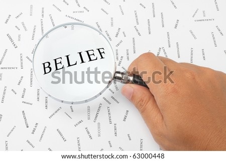 The word, BELIEF is magnified. - stock photo