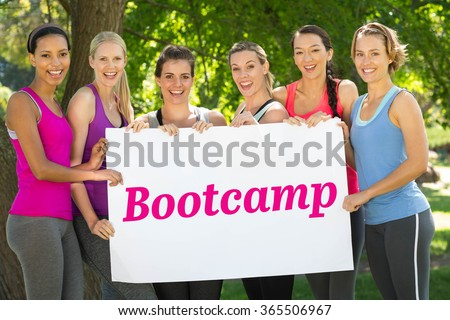 The word bootcamp and modern white and pink room with window against fitness group holding poster in park - stock photo