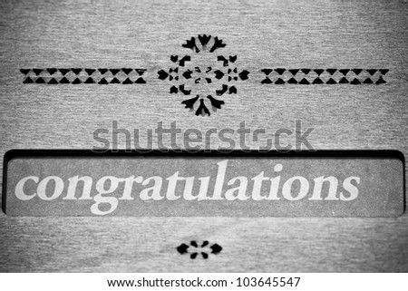 The word Congratulations is highlighted with a wooden decoration board in black and white - stock photo