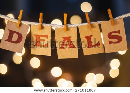 The word DEALS printed on clothespin clipped cards in front of defocused glowing lights. - stock photo