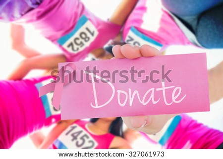 The word donate and young woman holding blank card against five smiling runners supporting breast cancer marathon - stock photo