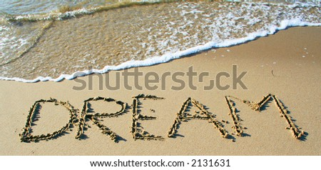 """The word """"dream"""" written in the sand. - stock photo"""