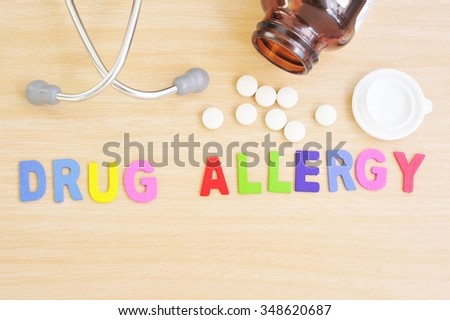 The word drug allergy written on a wooden background with pills and stethoscope.Drug allergy concept.  - stock photo