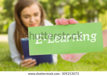 The word e-learning and hand showing card against university student lying and using tablet pc - stock photo
