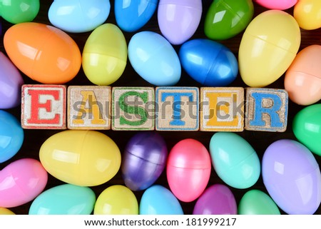 The word Easter spelled out in childrens toy blocks surrounded by a group of colorful plastic eggs. Horizontal format on a rustic wood background filling the frame. - stock photo