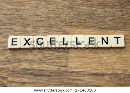 The word excellent written in tiles on a wooden surface - stock photo