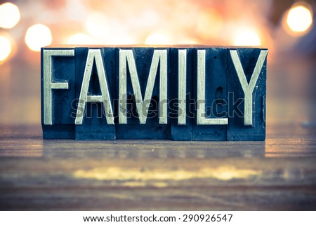 The word FAMILY written in vintage metal letterpress type on a soft backlit background. - stock photo