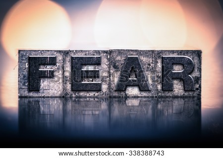 """The word """"FEAR"""" written in vintage ink stained letterpress type. - stock photo"""