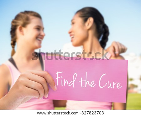 The word find the cure and hand holding card against two smiling women wearing pink for breast cancer - stock photo