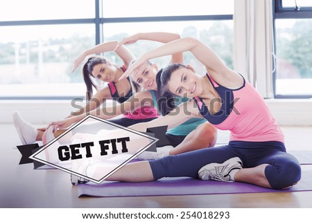 The word get fit and fitness class and instructor doing stretching pilate exercises against badge - stock photo