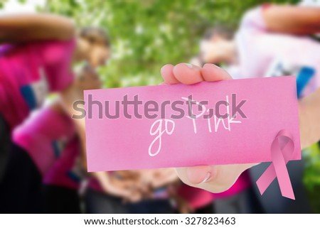 The word go pink and young woman holding blank card against smiling women running for breast cancer awareness - stock photo