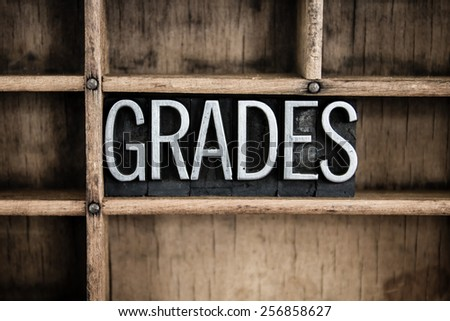 "The word ""GRADES"" written in vintage metal letterpress type in a wooden drawer with dividers. - stock photo"