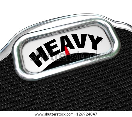 The word Heavy on the display of a scale in close-up, measuring weight or mass to determine if you are overweight and need to diet to improve your health and lose weight - stock photo