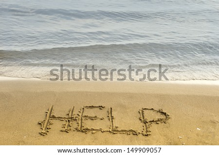 The word help is carved in the sand in the conceptual photo - stock photo