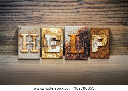 """The word """"HELP"""" written in rusty metal letterpress type sitting on a wooden ledge background. - stock photo"""