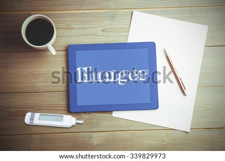 The word hunger and glucose monitor against high angle view of digital tablet and document with coffee - stock photo