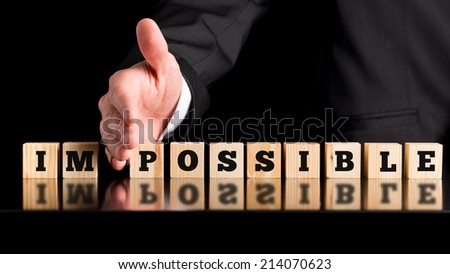 The word Im - Possible on a line wooden blocks separated by the hand of a businessman conceptual of all things being possible given enough input and effort, on a dark background with copyspace. - stock photo