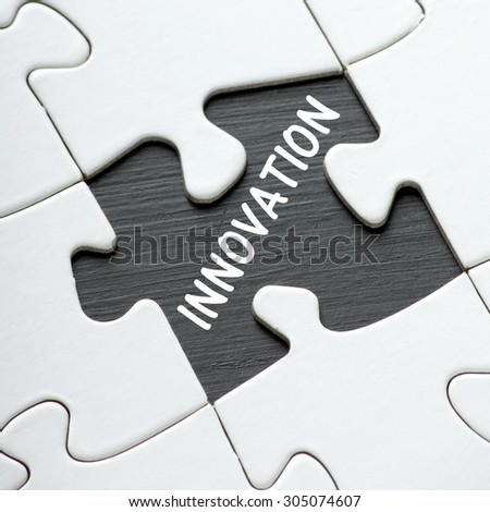The word Innovation in white text on a blackboard as revealed by a missing jigsaw puzzle piece - stock photo