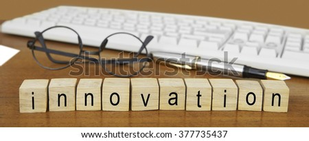 The word innovation on wood stamp stacking on desk with keyboard, vintage retro image style - stock photo