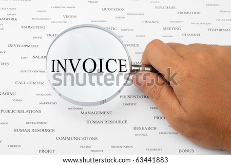 The word INVOICE is magnified. - stock photo