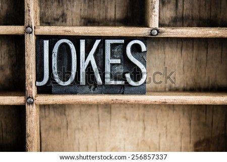 "The word ""JOKES"" written in vintage metal letterpress type in a wooden drawer with dividers. - stock photo"