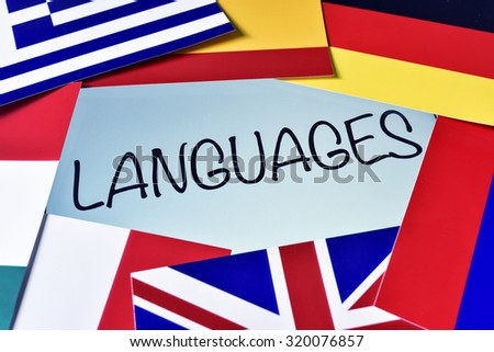 the word languages in the screen of a tablet computer surrounded by flags of different countries - stock photo