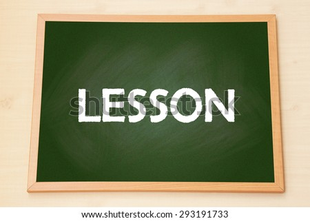 The word 'Lesson' on green chalkboard with wooden frame on wood background. - stock photo
