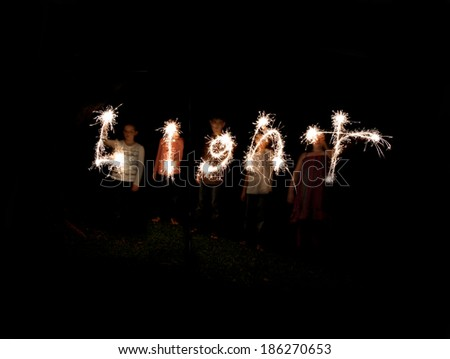The word light written with sparklers against a black background - stock photo